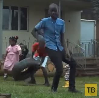 Африканские дети танцуют на заднем дворе дома...
