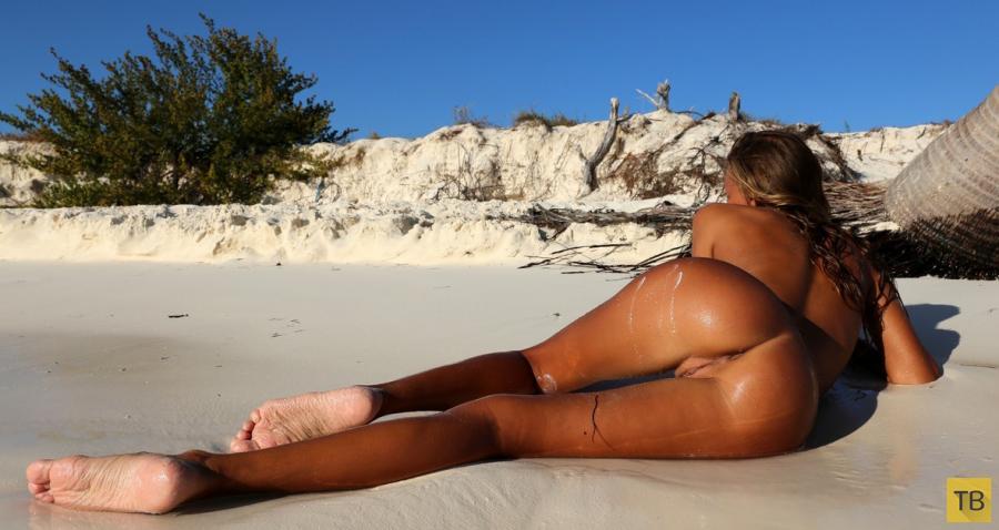Загорелая стройняшка греется на пляже (16 фото)